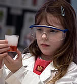 Child in lab coat and safety glasses