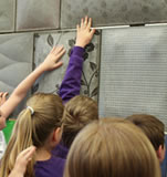 School pupils touch the fabric formed concrete wall