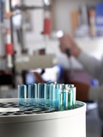 Test-tubes in foreground as researcher works in lab