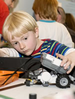 A child builds lego robots at Discover Science's 'Robofun'.