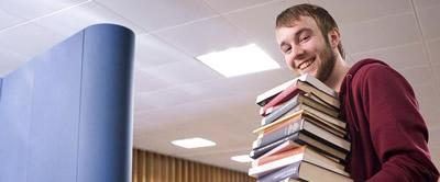 Student in library carrying a large stack of books