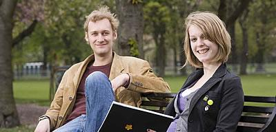 Postgraduate students sitting on a bench in George Square