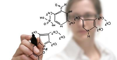 A chemist drawing a molecular structure on a whiteboard