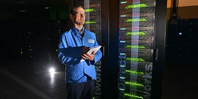 Photo of Luis Felipe Sopher de Popovics, Cray System Engineer, with the ARCHER supercomputer