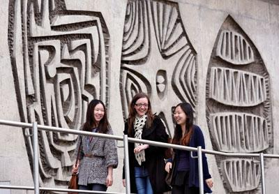 Photograph of our postgraduate students with backdrop of the amazing wall sculptures on our Charteris building