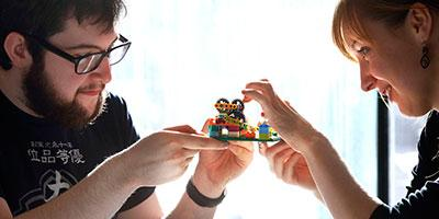Photo of two students working on a mechanical model