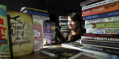 A student from the reading panel, surrounded by books submitted for the prize