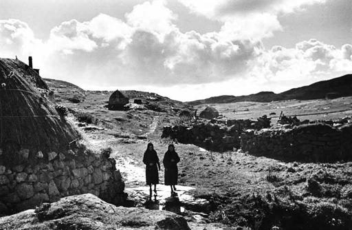 Two women walking near a blackhouse on Eriskay, 1936