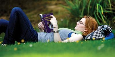 Student lying on grass reading a book