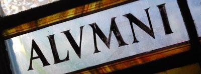"""Stained glass of the word """"alumni"""" in capitals, with the 'u' written as a 'v'"""