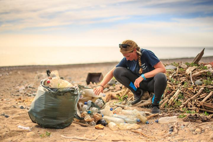 Cal Major sifting through plastic debris on a beach