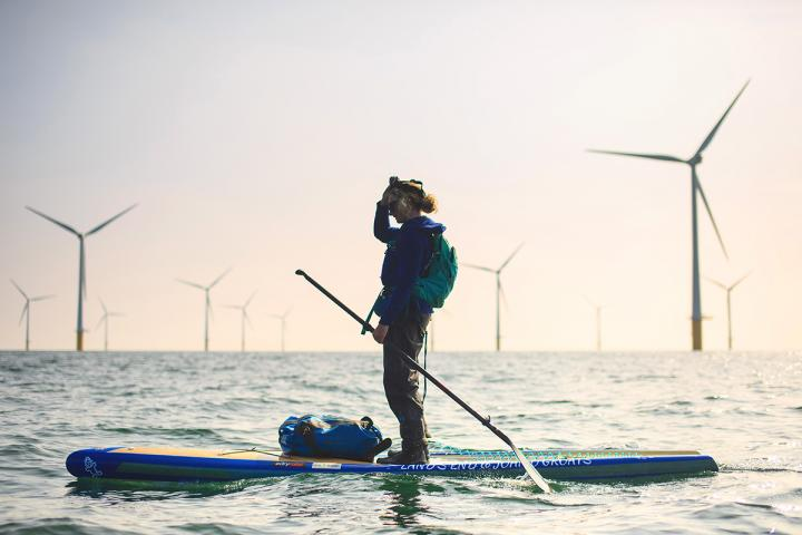 Cal on her paddleboard with wind turbines on the horizon