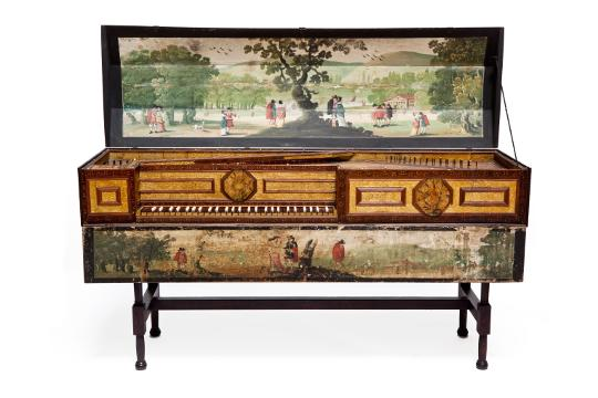 A wide shot of a virginal - an old keyboard instrument. It is large and rectangular with short legs and ornate panelling