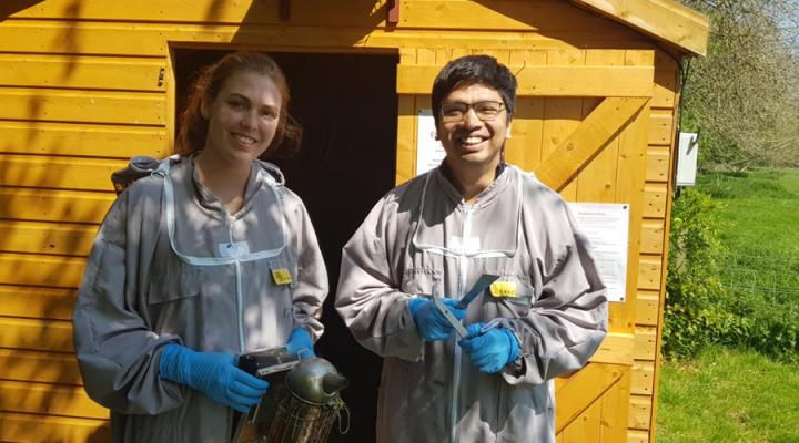 Students Abigail and Ani, wearing bee suits, stand outside a shed at the Easter Bush Campus Apiary.