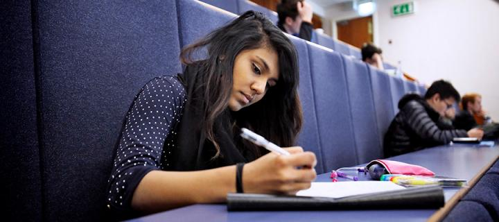 Undergraduate student taking notes during a lecture