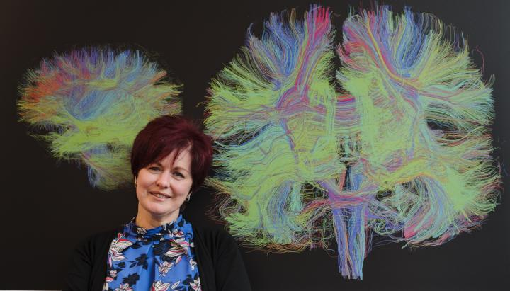Julie Duffus stands in front of a colourful MRI image of the brain