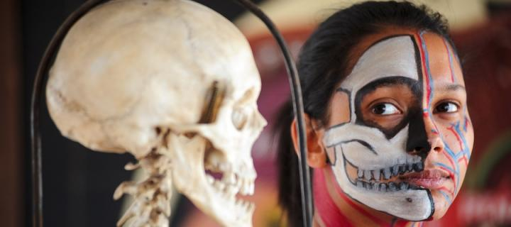A girl with her face painted with the image of a skull next to a skull