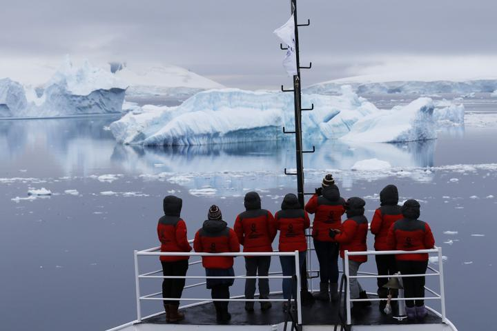 Antarctica expedition boat sailing past icebergs