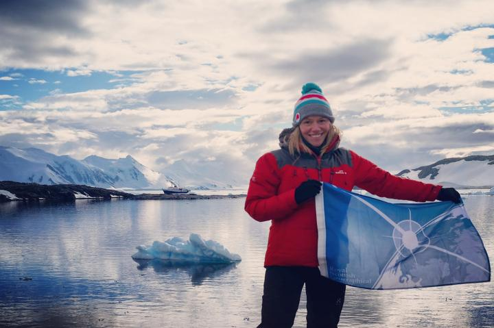 Beth Christie with flag in Antarctica