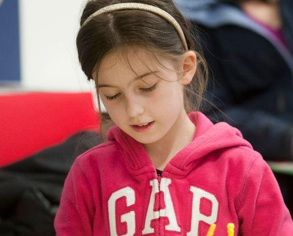 Young girl in a pink top focusing on designing a game