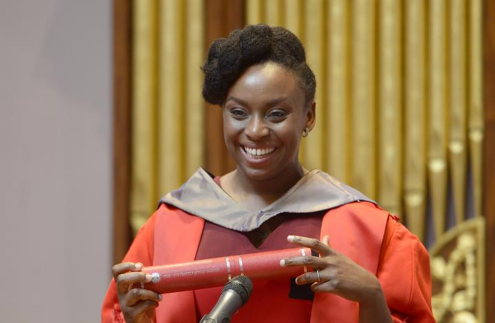 Chimamanda Ngozi Adichie holding her degree scroll