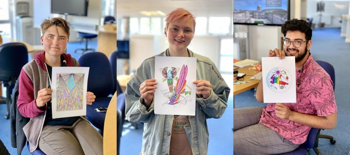 Three students holding up their brightly coloured-in illustrations