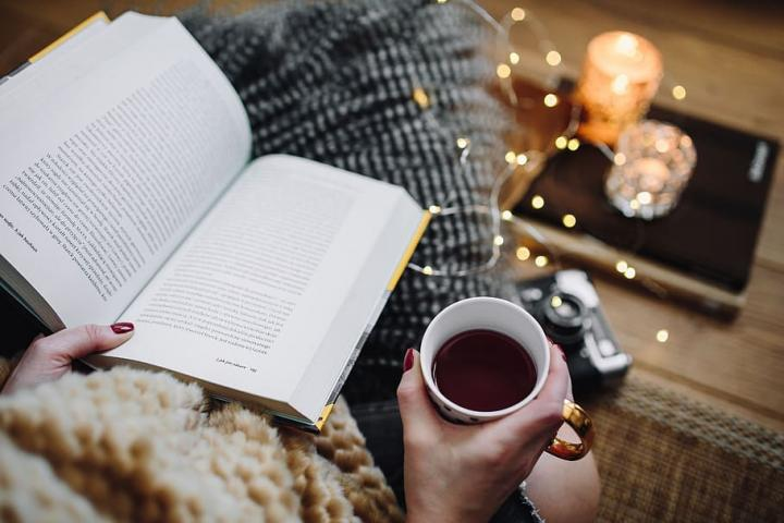 Photograph of a person drinking coffee while reading in a book in a cosy setting