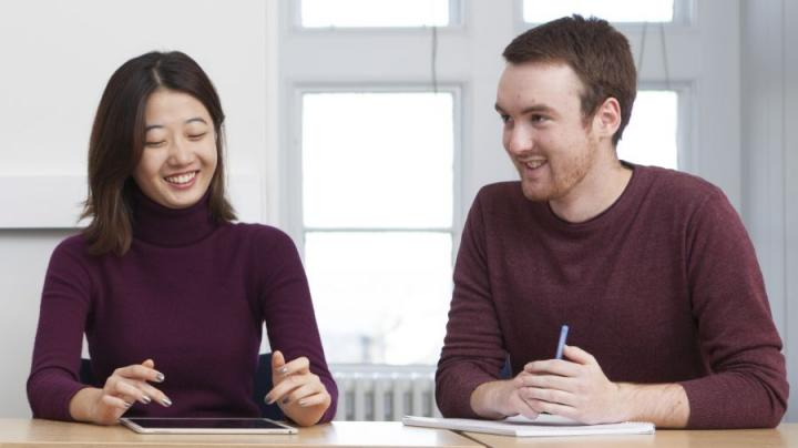 Divinity students Consuella Zhao and Euan Nicoll sitting at a table in a tutorial