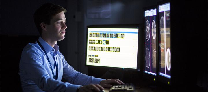 A consult neuroradiologist looking at a computer screen
