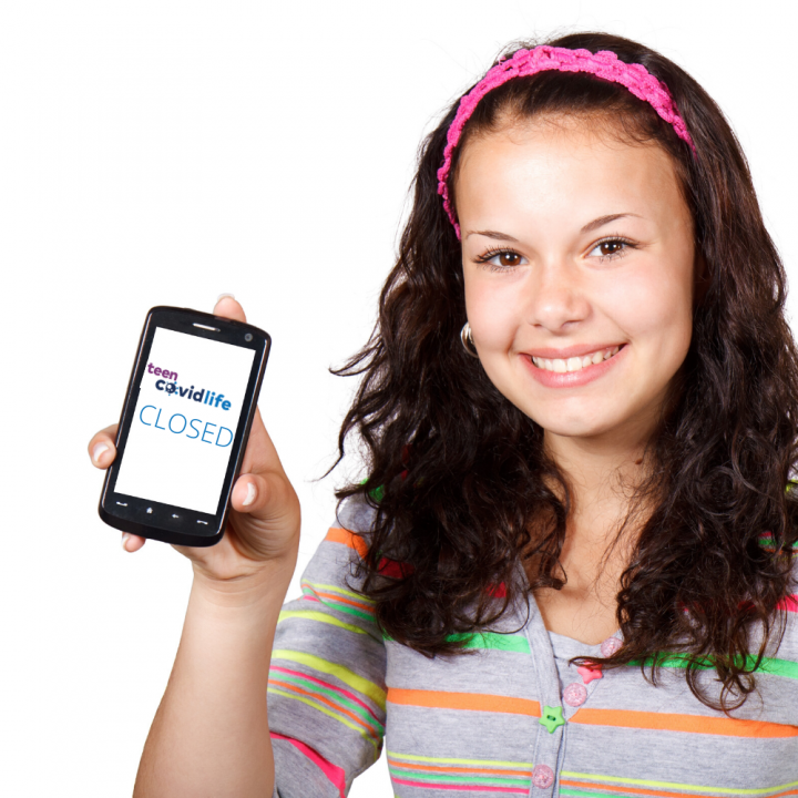 Female teenager holding a mobile with the TeenCovidLife Logo and the word closed underneath inside it
