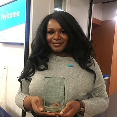 Photograph of Dominique Green holding her Equate Student-Institution Partnership Award