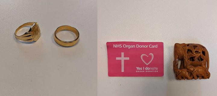 Gold signet ring and gold wedding ring, a pink donor card showing a crucifix and a small wooden carving of an elephant with two baby elephants.