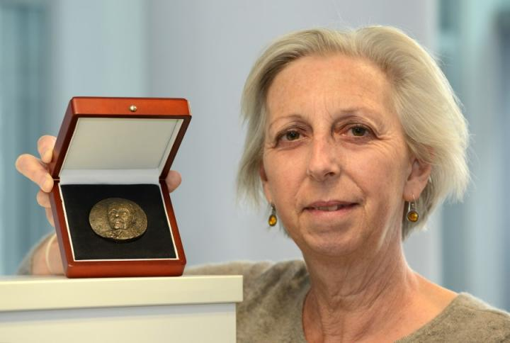 Professor Eleanor Riley holding the Ronald Ross Medal.