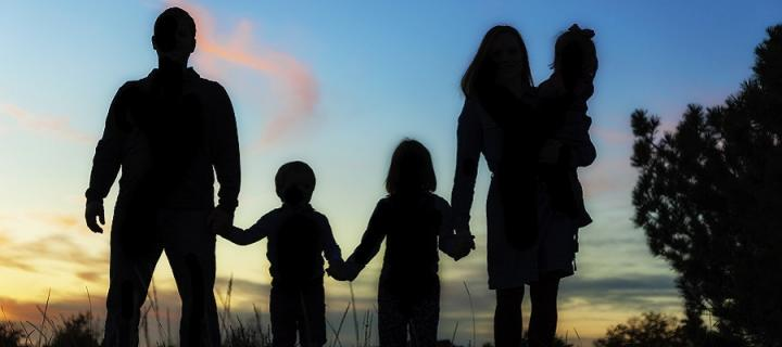 Family siloutted by sunset