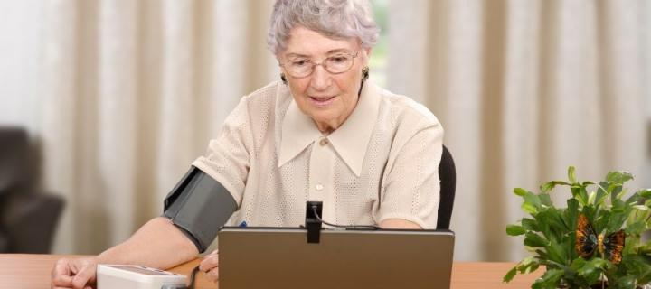 Elderly woman using a blood pressure machine while video calling on a laptop