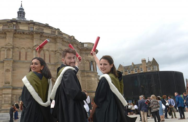 Three students in graduation robes outside McEwan Hall