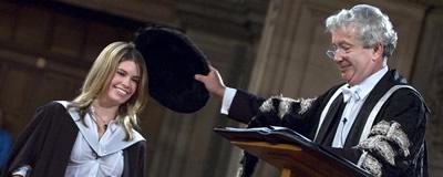 The prinicipal doffing the head of a student with the geneva bonnet to confer his degree
