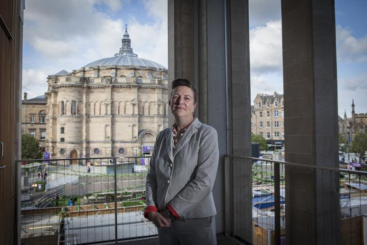 Gwen Orr stands with McEwan Hall and Bristo Square in the background