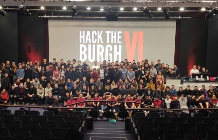 Photo of all the participants of the Hack the Burgh VI, stood on a stage in front of the event logo.