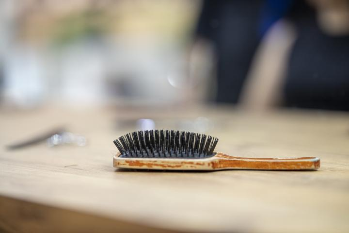 Photograph of a wooden hair brush with black bristles lying on a table.