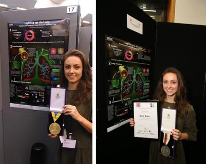 PhD student Helen Parker stands next to her poster, holding her gold medal and certificate
