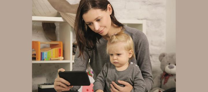 a woman looking at a phone screen, with a child sitting on her lap
