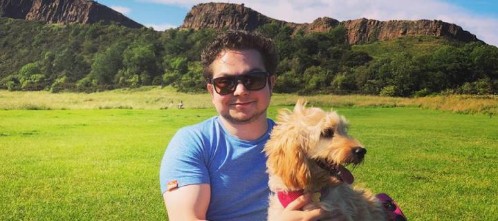Ian LeBruce and his dog in Holyrood Park with the Crags in the background.