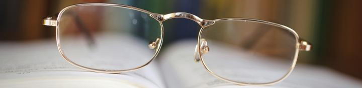 Spectacles lying on open book