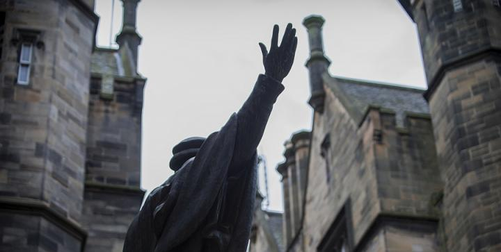 Looking up towards the outstretched hand of the stature of John Knox in New College quad