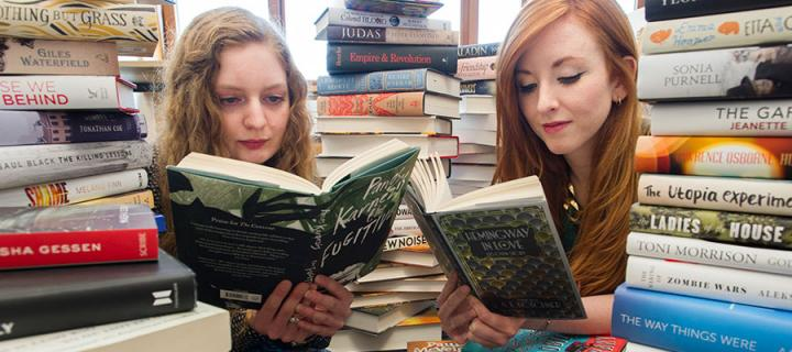 Photo of The James Tait Black Prize co-ordinators Mhairi Morrison and Rosaleen Nolan, both reading books