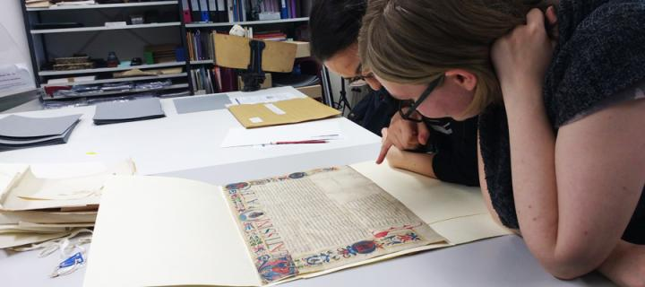 A student studies one of the manuscripts from the Laing collection