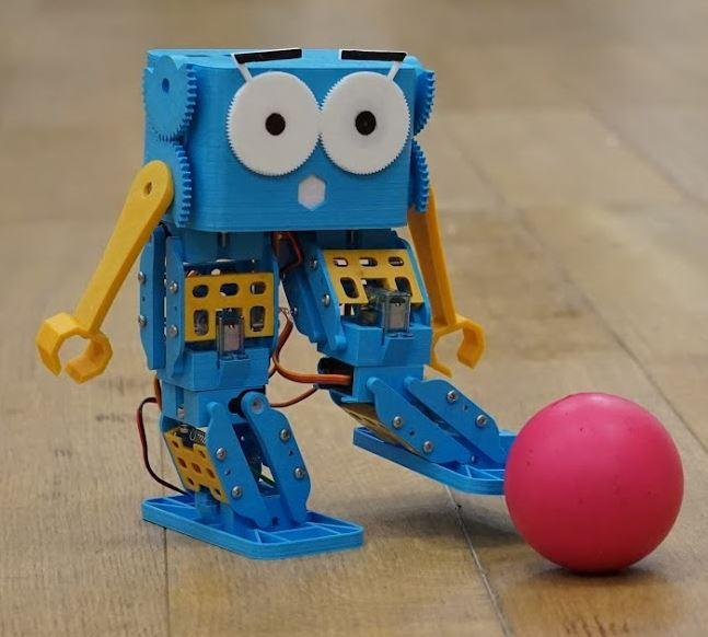 Marty the little blue robot kicking a ball
