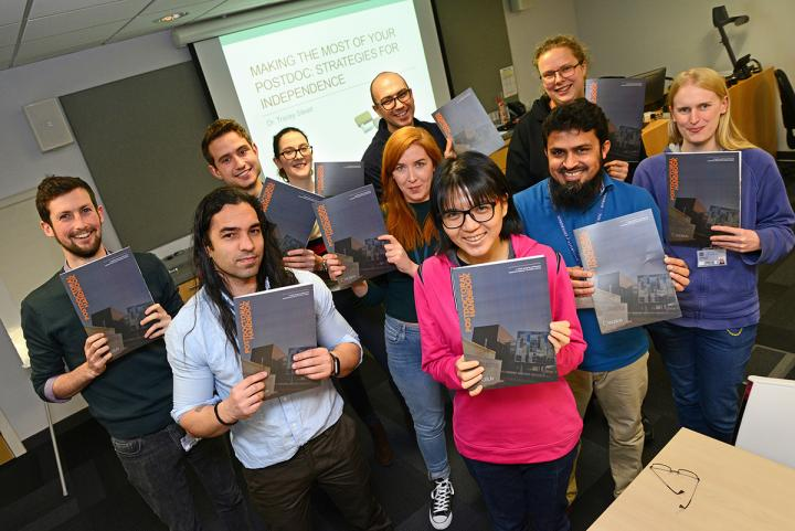 Several people holding up a copy of the postdoc handbook.