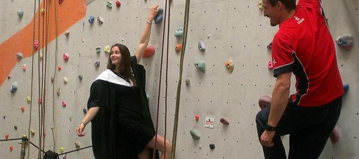 Natalie Berry on the climbing wall in her graduation robe